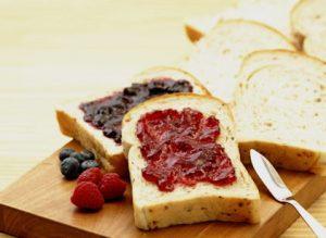パンにたっぷりのジャムをつけて食べる